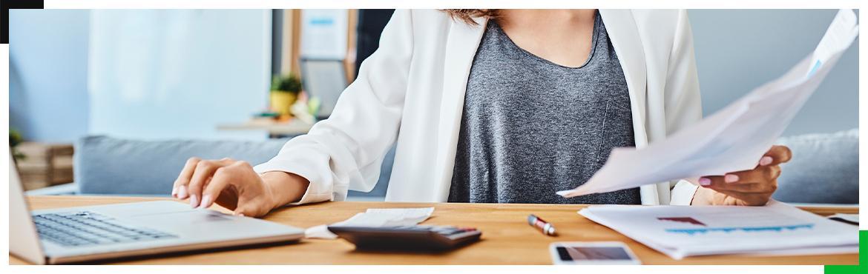 kobieta trzymająca dokument i pisząca na laptopie